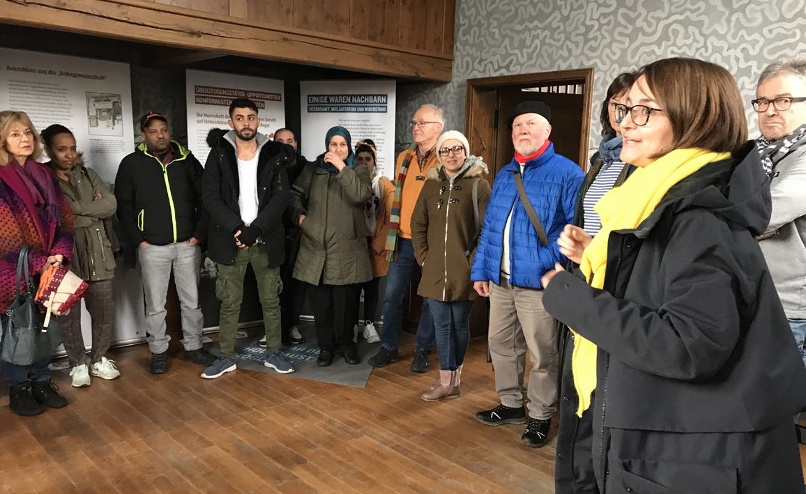 Manon Pirags erzählt Mitgliedern des Asylkreises Bork und Flüchtlingen, die deutsch lernen, die Ausstellung in der alten Synagoge